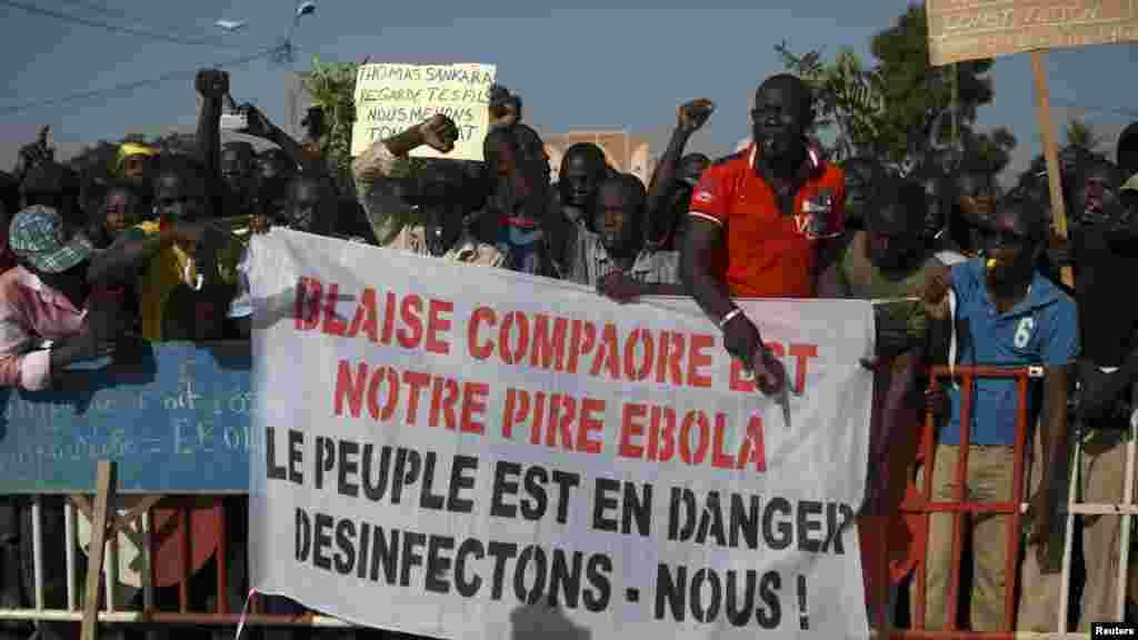 """Des manifestants tiennent une banderole avec la mention : """"Blaise Compaoré est notre Ebola"""", sur la place de la Révolution, Ouagadougou, 28 octobre 2014. (REUTERS/Joe Penney)"""