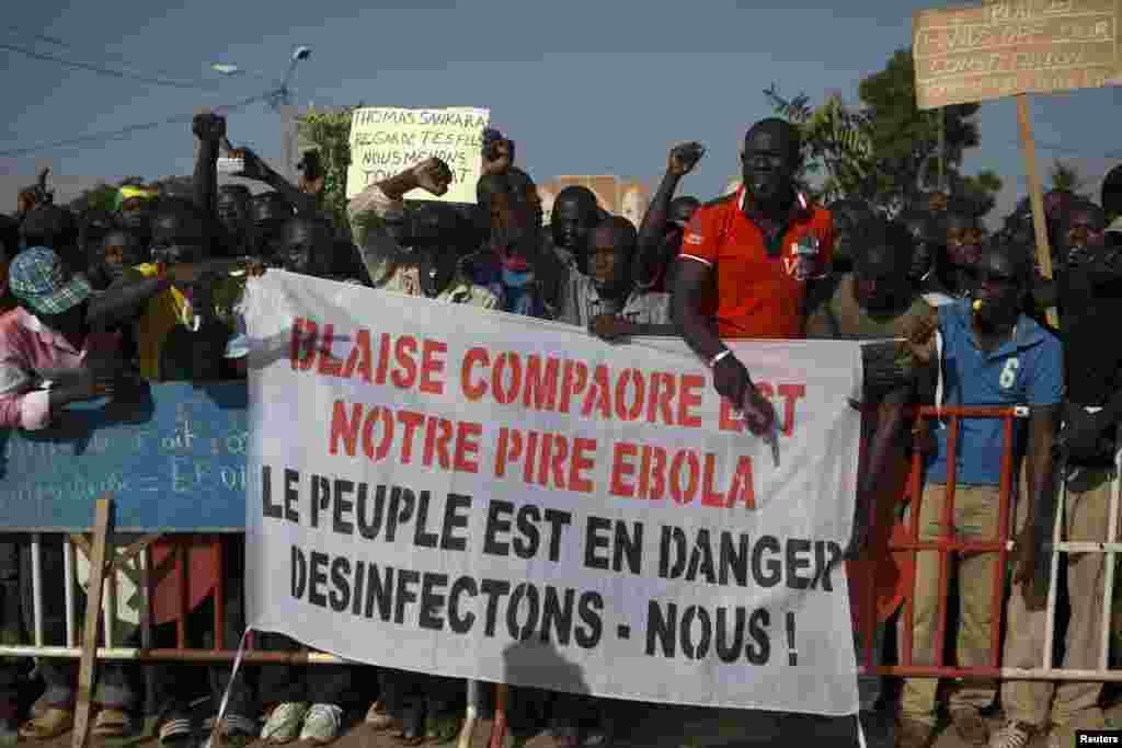 """Des manifestants tiennent avec une banderole avec la mention """"Balise Compaoré est notre Ebola: Le peuple est en danger, désinfectons-nous!» à Ouagadougou, Burkina Faso, le 20 octobre 2014. La police a lancé des grenades à gaz lacrymogène aux manifestants qui ont usé des pierres à la fin d'une manifestation qui avait regroupé des dizaines de milliers de gens. REUTERS/Joe Penney"""