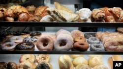 FILE - A selection of pastries, including doughnuts, bagels, rolls, croissants, turnovers and sticky buns are displayed in a New York coffee cart. In studies of mice fed fatty, Western-style diets putting them at risk for heart disease, researchers showed that AT04A reduced the total amount of cholesterol by 53 percent.