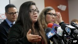 Marlene Mosqueda (left) whose father was arrested by ICE agents early Friday morning, talks at a news conference with her attorney Karla Navarrette, Feb. 10, 2017. Navarrete said another lawyer filed federal court papers to halt his removal.