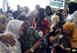 Relatives of passengers comfort each other as they wait for news on a Lion Air plane that crashed off Java Island at Depati Amir Airport in Pangkal Pinang, Indonesia Monday, Oct. 29, 2018.