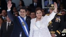El nuevo presidente de Honduras, Juan Orlando Hernández, y la primera dama, Ana Rosalinda, saludan luego de la ceremonia de juramentación en el Estadio Nacional de Tegucigalpa.