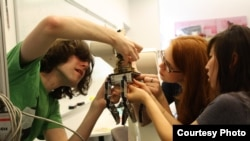 Students in the Mechanical Prototyping class at Olin College work on a robotic hand.