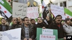 "Syrians living in Turkey and human right activists stage a protest outside the Syrian consulate to condemn the latest killings in Syria, in Istanbul, Turkey, Saturday, Feb. 4, 2012. The banners read: ""Assad has arms, we have God"" and "" Syrian Turkmen comm"