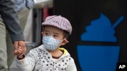 2016年10月14日,北京一名儿童戴口罩。北京市空气重污染应急指挥部办公室在下午将蓝色预警提升至黄色预警,北京城区PM2.5浓度接近每立方米350微克,达到6级严重污染