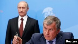Russia's President Vladimir Putin (back) and Rosneft CEO Igor Sechin attend a signing ceremony at the St. Petersburg International Economic Forum 2014 in St. Petersburg, May 24, 2014.