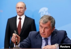 FILE - Russia's President Vladimir Putin, left, and Rosneft CEO Igor Sechin attend a signing ceremony at the St. Petersburg International Economic Forum 2014 in St. Petersburg, May 24, 2014.
