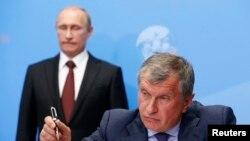 ولادیمیر پوتین، رئیس جمهور روسیه، (در عقب) و مدیر عامل شرکت روسنفت، ایگور سچین، در مراسم امضای قرارداد در انجمن بین المللی اقتصادی در سن پترزبورگ – ۳ خرداد ۱۳۹۳ (۲۴ مه ۲۰۱۴)