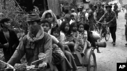 Cambodian women and children fill the back of a motorcycle taxi carrying them to safer parts of Phnom Penh as Khmer Rouge insurgents continue their artillery shelling of the capital, January, 28,1974. (AP Photo)