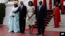 Shugaban Amurka Barack Obama yana daga hannu, a lokacin da yake jiran a dauke su a hoto, tare da mai dakin shi Michelle, da Shugaban Senegalt Macky Sall, dama, da mai dakin shi Mariame Faye Sall, a fadaar Shugaban kasa dake Dakar Senegal. Alhamis