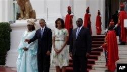 Presiden Obama (melambaikan tangan) dan ibu negara AS Michelle Obama (dua dari kanan) didampingi Presiden Senegal Macky Sall (kanan) dan ibu negara Senegal Mariame Faye Sall,di istana kepresidenan Senegal di Dakar (27/6).