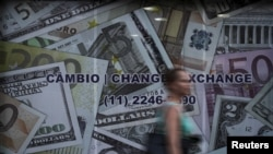 FILE - A woman walks past a currency exchange office in Sao Paulo, Brazil, Jan. 7, 2016.