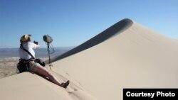 """Seorang teknisi suara memasang peralatannya untuk merekam """"nyanyian"""" bukit pasir di Gurun Mohave, California. (Foto: Trevor Cox)"""