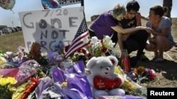 Isaac Pacheco (giữa) đặt tấm thiệp chúc mừng sinh nhật cho Alex Sullivan, người bạn đã chết trong vụ nổ súng, tại địa điểm tưởng niệm nạn nhân bên ngoài rạp chiếu phim