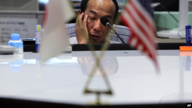 A money trader waits for calls from clients during the morning trading at a money brokerage in Tokyo Monday, Aug. 8, 2011.