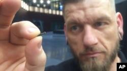 """El autodefinido """"hacker del cuerpo"""" Jowan Osterlund de Biohax Sweden, sostiene un pequeño implante de microchip, similar al implantado en trabajadores de Epicenter, en Estocolmo, Suecia."""