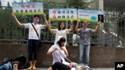 FILE - Gay rights campaigners act out electric shock treatment to protest outside a court where the first court case in China involving so-called conversion therapy is held in Beijing, China, July 31, 2014. A gay man in Henan province has now successfully sued a mental hospital over forced conversion therapy.
