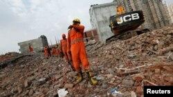 지난 17일 건물이 무너져 내린 현장에서 인부들이 작업을 하고 있다.