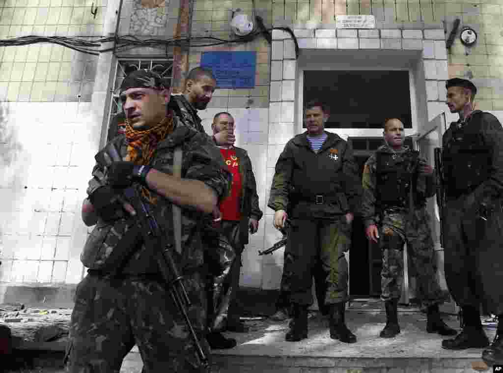 Alexander Zakharchenko, center, the leader of pro-Russian rebels in Donetsk, observes the damage at a school after shelling in Donetsk, eastern Ukraine, Oct. 1, 2014.