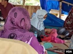 Pengungsi perempuan asal Afghanistan sedang menyulam di tenda pengungsi seberang Rudenim Jakarta hari Rabu (19/6). (Foto: VOA/Sasmito)