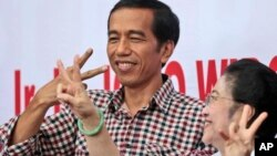 Calon presiden Joko Widodo dan mantan presiden sekaligus ketua Partai Demokrasi Indonesia Perjuangan Megawati Sukarnoputri. (AP/Dita Alangkara)