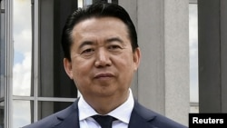 FILE - Then-Interpol chief Meng Hongwei poses during a visit to the headquarters of International Police Organization in Lyon, France, May 8, 2018.