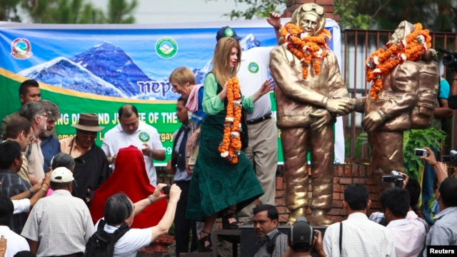 Amelia Rose Hillary (C) walks to place a garland on statues of her grandfather Sir Edmund Hillary (L) and Tenzing Norgay Sherpa (R), in Kathmandu, May 29, 2013.