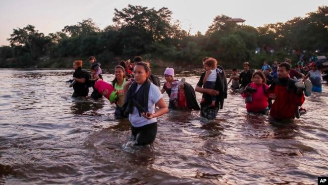 Los migrantes centroamericanos cruzan el río Suchiate desde Guatemana hacia México el 23 de enero de 2020 con el agua hasta la cintura por un sector donde no había tropas mexicanas cuidando la frontera.