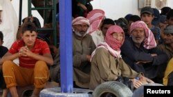 FILE - Syrian refugees wait to board a Jordanian army vehicle after crossing into Jordanian territory with their families, in al-Ruqban border area, near the northeastern Jordanian border with Syria, and Iraq, near the town of Ruwaished, 240 km (149 miles) east of Amman, Sept. 10, 2015.