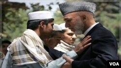 Presiden afghanistan Hamid Karzai menyalami anak-anak yang direkrut Taliban untuk melakukan serangan bunuh diri (24/8). Karzai memerintahkan ke-20 anak dikembalikan kepada orang-tuanya.