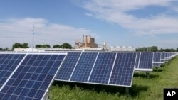A solar panel array collects sunlight with the Fremont, Neb., power plant seen behind it, May 31, 2018. Solar energy is gaining traction in a small but growing number of Nebraska cities, but the technology still faces a number of obstacles that is keeping