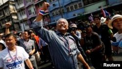 Protest leader Suthep Thaugsuban (C) greets his supporters as he leads thousands of anti-government demonstrators marching in Bangkok, Thailand Jan. 9, 2014.