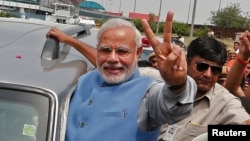 Hindu nationalist Narendra Modi, the prime ministerial candidate for India's Bharatiya Janata Party (BJP), gestures towards his supporters from his car during a road show upon his arrival at the airport in New Delhi, May 17, 2014.