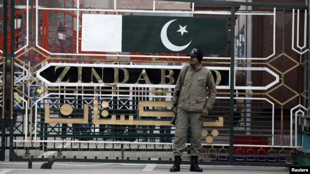 A paramilitary soldier stands guard beside a border gate at the India-Pakistan joint check-post at the Wagah border near Lahore, January 6, 2013.