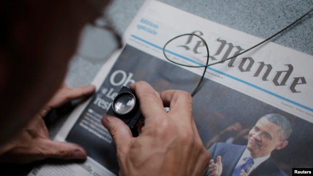 FILE - An employee checks a copy of the freshly-printed French daily evening newspaper Le Monde which announces the re-election of U.S. President Barack Obama, Paris, November 7, 2012.