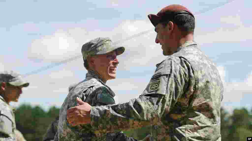 La première lieutenant Shaye Haver, à gauche, est félicitée par un soldat non identifié avant une cérémonie de remise des diplômes de l'école des Rangers de l'armée américaine vendredi 21 août 2015, à Fort Benning, en Géorgie.