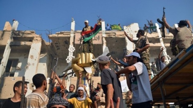 Rebels and their supporters celebrate around the iconic statue of a golden fist crushing a US military bomber outside Libyan leader Moammar Gadhafi's heavily damaged Bab al-Azizya compound in the center of Tripoli on August 24, 2011