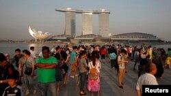 Para wisatawan menikmati suasana di Marina Bay Singapura setelah Sabtu (22/6). Kualitas udara di Sigapura dilaporkan membaik, Minggu (23/6), setelah pemerintah Indonesia melakukan upaya pemadaman kebakaran hutan dengan menjatuhkan bom air.