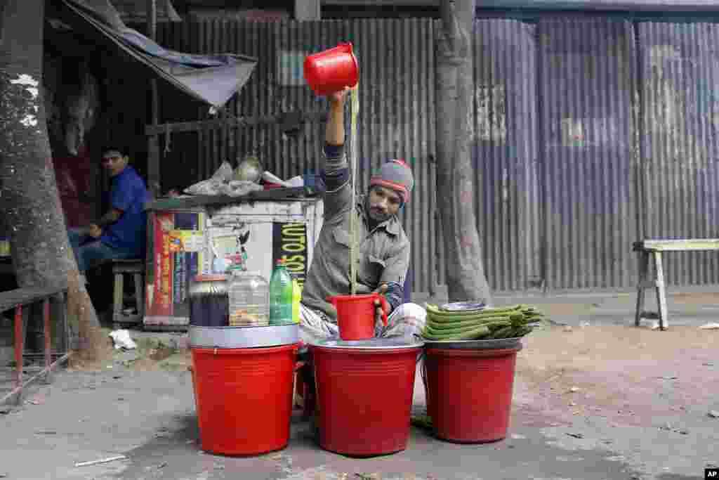 A street vendor prepares herbal juice for sale in Dhaka, Bangladesh.