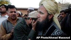 People comfort a man who lost his family member in a suicide attack in Mardan, Pakistan, on Dec. 29, 2015.