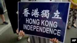 A protester raises a placard during a protest outside the police headquarter in Hong Kong, Sept. 25, 2018.