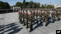 Members of pro-defense forces attend a parade in front of the Tomb of the Unknown Soldier during the first nationwide rally, in Warsaw, Poland, Thursday, Sept. 17, 2015.