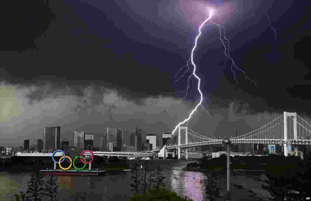 Lightning illuminates the sky over the Olympic rings and the Rainbow Bridge in Tokyo, Japan.