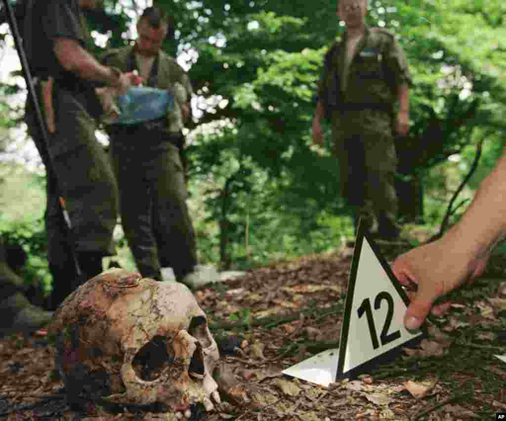 Photo shows a Finnish forensic expert placing a number next to the skull of a Srebrenica victim found in the hills above the village of Kravice, some 15 kms (10 miles) north west of Srebrenica.(File 2006)