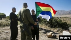 FILE - A member of the Druze community holds a Druze flag as he speaks to an Israeli soldier near the border fence between Syria and the Israeli-occupied Golan Heights, near Majdal Shams, June 18, 2015.