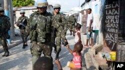 des soldats de la paix du Brésil saluent des enfants en patrouillant dans le bidonville de Cité Soleil, à Port-au-Prince, Haïti, 22 février 2017.