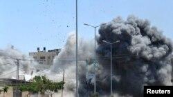 加沙城一座房屋起火,目击者说是以色列袭击造成的。