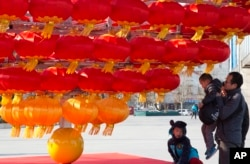 FILE - A man lifts a child up to lantern decorations setup ahead of the Chinese New Year in Beijing, China.