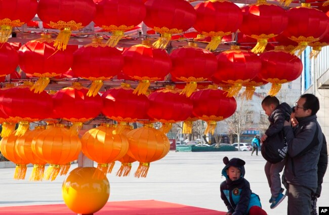 A man lifts a child up to lantern decorations setup ahead of the Chinese New Year in Beijing, China.