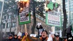 Người Nam Triều Tiên đốt áp phích trong cuộc biểu tình chống Thủ tướng Nhật Bản Shinzo Abe trước cửaa Đại sứ quán Nhật Bản ở Seoul.